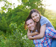Couples de sourire heureux dans la forêt. Coucher du soleil Photos stock
