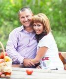 Couples de sourire heureux dans la forêt d'automne sur le pique-nique Images stock