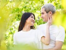 Couples de sourire heureux dans le jardin d'amour au printemps Image stock