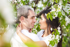 Couples de sourire heureux dans le jardin d'amour au printemps Photographie stock libre de droits
