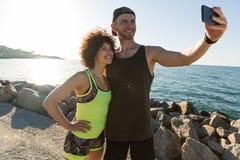 Couples de sourire heureux de forme physique dans les vêtements de sport prenant un selfie Image libre de droits