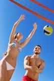 Couples de sourire heureux jouant le volleyball Photos libres de droits