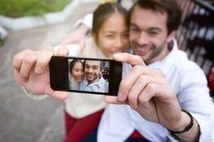 Couples de sourire heureux prenant le selfie dehors Photographie stock