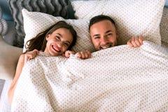 Couples de sourire heureux se situant dans le lit à la maison photographie stock