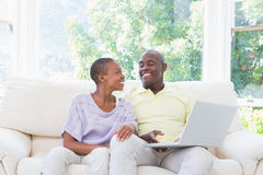 Couples de sourire heureux utilisant l'ordinateur portable sur le divan Images libres de droits