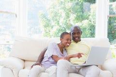 Couples de sourire heureux utilisant l'ordinateur portable sur le divan Image stock