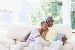 Couples de sourire heureux utilisant l'ordinateur portable sur le divan Photographie stock libre de droits
