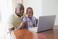 Couples de sourire heureux utilisant leur ordinateur portable Photo libre de droits