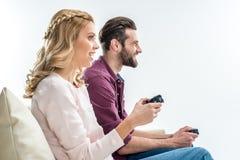 Couples de sourire jouant avec des manettes Images stock