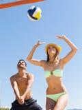 Couples de sourire jouant le volleyball Photographie stock libre de droits