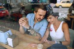 Couples de sourire joyeux parlant en café derrière la fenêtre Images libres de droits