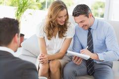 Couples de sourire lors de la réunion avec un conseiller financier Photos libres de droits