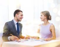 Couples de sourire mangeant des sushi au restaurant Photo libre de droits