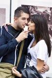 Couples de sourire mangeant la crème glacée sur la rue Image stock