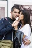 Couples de sourire mangeant la crème glacée sur la rue Image libre de droits