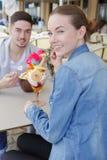 Couples de sourire mangeant la crème glacée sur la terrasse Photographie stock