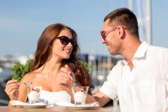 Couples de sourire mangeant le dessert au café Images stock