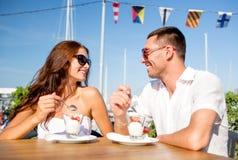 Couples de sourire mangeant le dessert au café Photos libres de droits