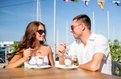 Couples de sourire mangeant le dessert au café Photographie stock