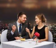 Couples de sourire mangeant le dessert au restaurant Photo stock