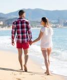 Couples de sourire marchant sur la plage Images libres de droits