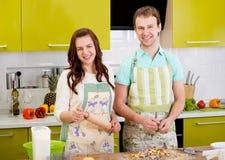 Couples de sourire Married faisant cuire la tarte aux pommes à la cuisine à la maison Photos stock