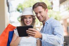 Couples de sourire mignons regardant un comprimé Photographie stock