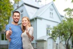 Couples de sourire montrant des pouces au-dessus de maison Photos stock