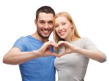 Couples de sourire montrant le coeur avec des mains Image stock