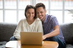 Couples de sourire observant la vidéo drôle sur l'ordinateur portable ou faire l'appel visuel Image stock