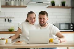 Couples de sourire observant la vidéo drôle sur l'ordinateur tout en ayant le bre image stock