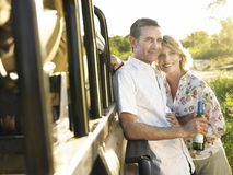 Couples de sourire par Jeep With Wine Bottle Photo stock