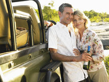 Couples de sourire par Jeep With Wine Bottle Photographie stock