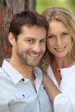 Couples de sourire par l'arbre Image stock