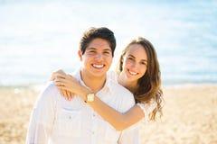 Couples de sourire par la mer un été ensoleillé, jour d'automne Photographie stock
