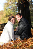 Couples de sourire parmi des lames d'automne Photo stock