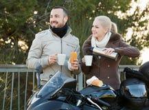 Couples de sourire positifs ayant le pique-nique avec du café Photographie stock