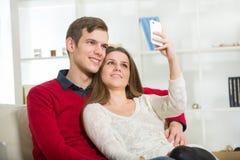 Couples de sourire prenant la photo d'autoportrait avec le téléphone à la maison Photos stock