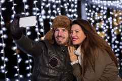 Couples de sourire prenant le selfie avec le téléphone intelligent à la patinoire Photo stock