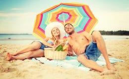 Couples de sourire prenant un bain de soleil sur la plage Photos libres de droits
