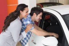Couples de sourire regardant à l'intérieur d'une voiture Photos libres de droits