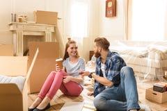 Couples de sourire regardant l'un l'autre tout en se reposant sur le plancher près des boîtes en carton Photo libre de droits
