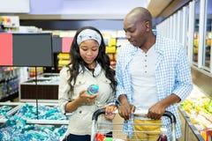 Couples de sourire regardant la bouteille de l'eau la section d'épicerie Images stock