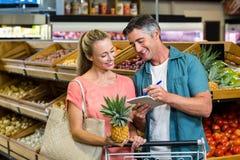 Couples de sourire regardant la liste d'épicerie Photos libres de droits