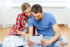 Couples de sourire regardant le PC de comprimé à la maison Photographie stock