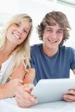 Couples de sourire retenant une tablette et regarder l'appareil-photo Photo libre de droits