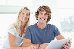 Couples de sourire retenant une tablette et regarder l'appareil-photo Photographie stock libre de droits