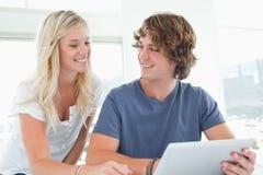 Couples de sourire retenant une tablette et regarder l'un l'autre Images libres de droits