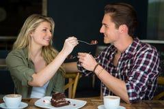 Couples de sourire s'alimentant le dessert en café Photographie stock
