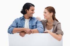 Couples de sourire se penchant sur le mur vide Photographie stock